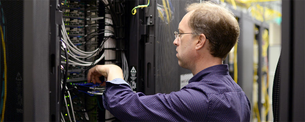 Staff member (Lori) works on data cabling in a server rack.