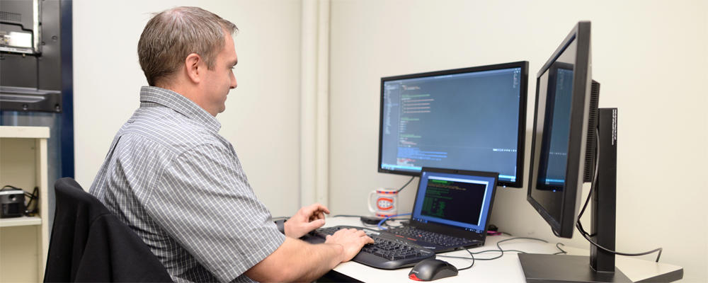 Staff member (Todd) works on some code at a workstation with three displays and a Montreal Canadiens mug.