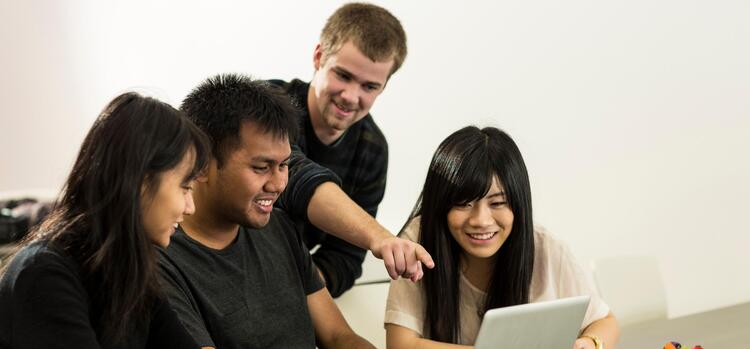 Four students working together on a laptop
