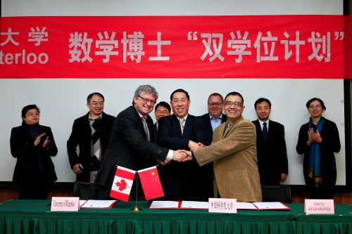 Representatives from the University of Waterloo and from the Chinese Academy of Sciences shaking hands