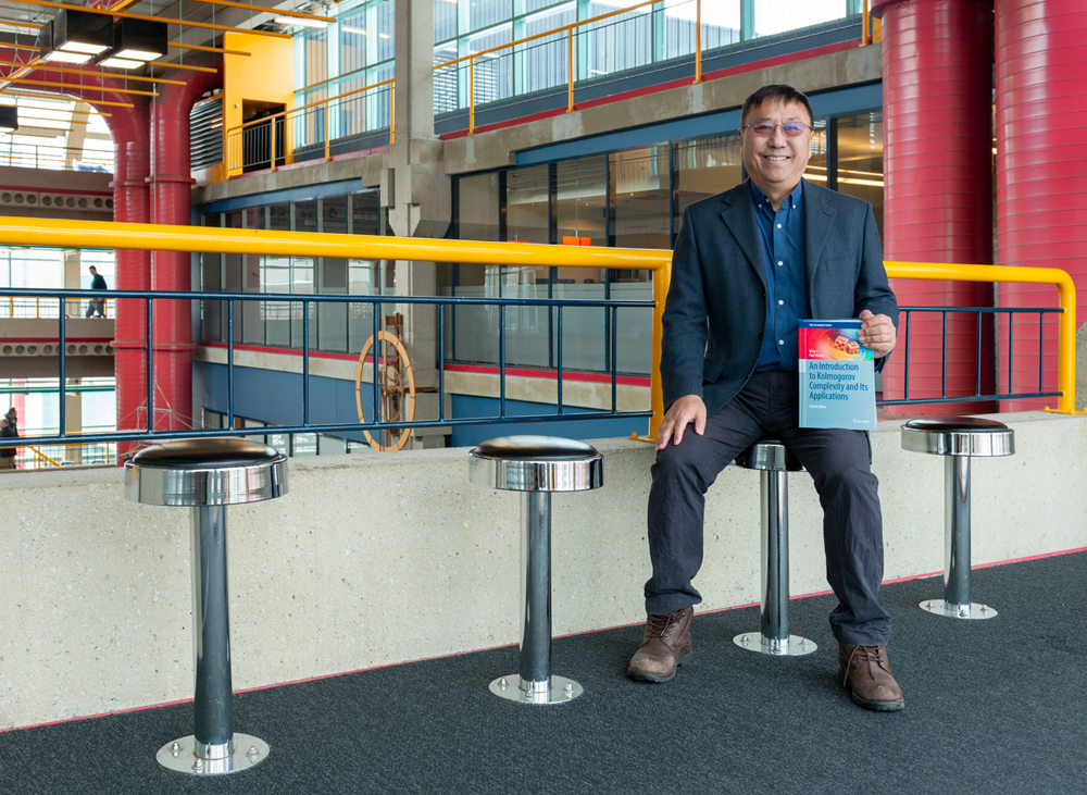 University Professor Ming Li holding Kolmogorov complexity book