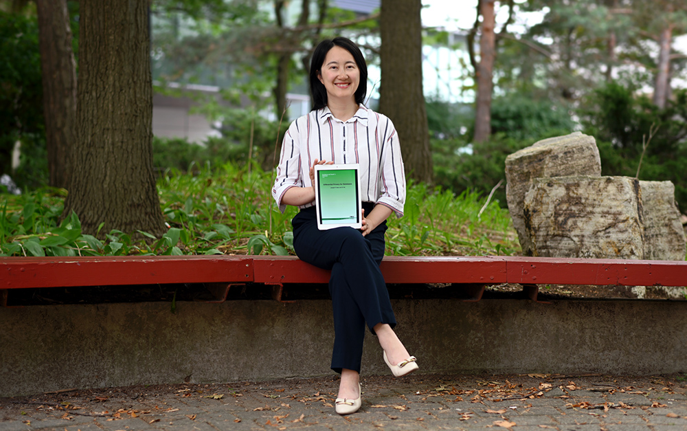 photo of Professor Xi He holding her book, Differential Privacy for Databases